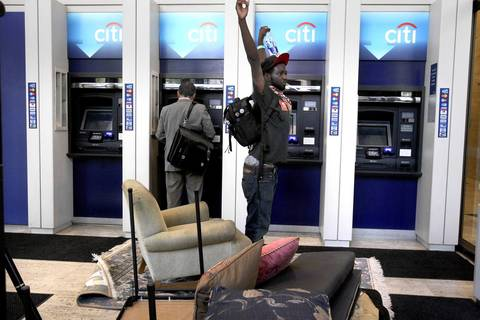 Protesters dumped old furniture into a Citi Bank ATM lobby across from Daley Plaza in Chicago after their protest about foreclosures and evictions. One protester stretches before sitting down momentarily before Chicago police arrive.