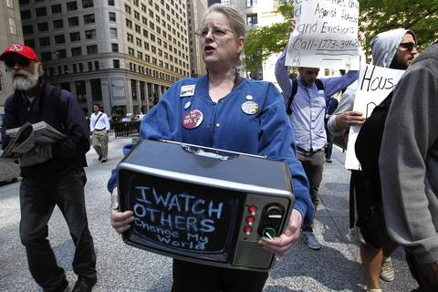 Grace Lloyd of Chicago carries a TV as part of a protesters marching from Jackson and LaSalle Streets in Chicago to Daley Plaza. They were protesting foreclosures and evictions.
