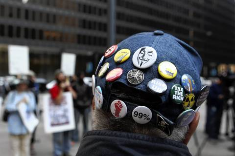 Buttons cover the cap of protester Ronald Schupp of Chicago's Uptown neighborhood as he rallies in support of civil rights activist Carlos Montes at Federal Plaza in downtown Chicago.