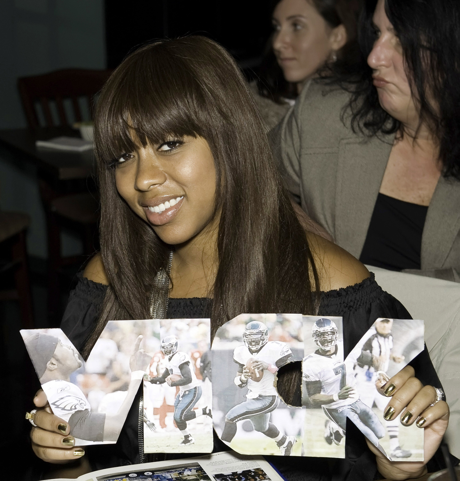 Philadelphia Eagles quarterback Michael Vick's fiancee Kijafa Frink holds up pictures of her husband to be.
