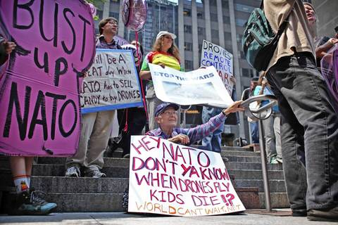 """Caroline Herzenberg, 80, of Chicago, sits on the steps of Prudential 2 Plaza with other protesters rallying against NATO and the use of drones. """"I'm just a sympathetic citizen,"""" Herzenberg said."""