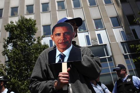 A protester covers his face with a cut out of President Barak Obama as protesters rally against NATO and the use of drones in front of Prudential 1 Plaza, the campaign headquarters of President Barak Obama.