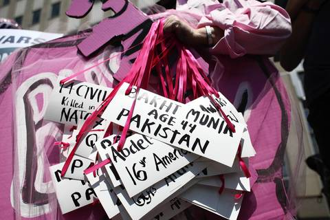 A protester holds up signs containing the names of people allegedly killed by drone strikes as a march is held against NATO and the use of drones in front of Prudential 1 Plaza, the campaign headquarters of President Barak Obama.