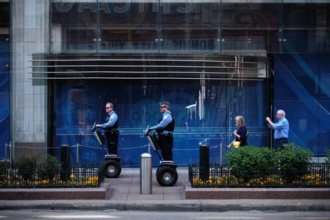 Chicago Police Dept. officers make their way past ABC-Channel 7 studios on State Street in Chicago.