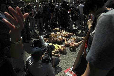 """Protesters perform an """"oily die-in"""" in front of the Canadian Consulate on East Lake Street as they rally against a pipeline that would bring Canadian tar sands for refining in the U.S."""