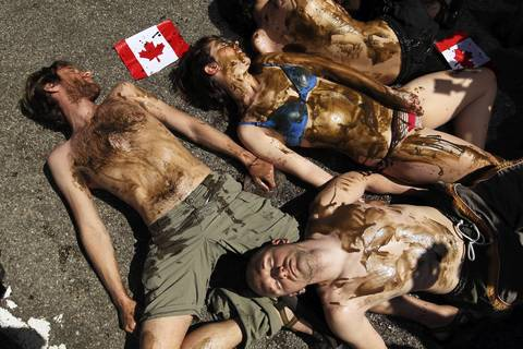 "Protesters perform an ""oily die-in"" in front of the Canadian Consulate on East Lake Street as they rally against a pipeline that would bring Canadian tar sands for refining in the U.S."