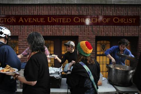 Volunteers with Seeds of Peace feed the dozens of protesters that arrived from out of town, outside of Wellington Avenue United Church of Christ in Chicago.