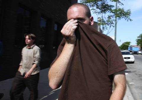 One of four people picked up Wednesday night in the Bridgeport neighborhood, allegedly suspected of either possessing or making Molotov cocktails, hides his face as he leaves the Harrison District police station. According to their lawyers, the four were released without charges.