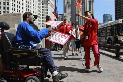 Veteran Anthony Kearse cheers on marchers as they walk up Michigan Avenue toward Daley Plaza for the National Nurses United protest.