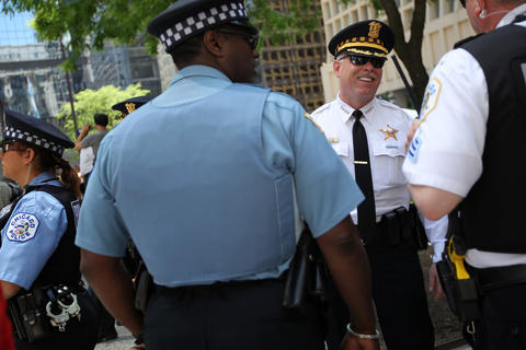 Chicago Police Superintendent Garry McCarthy chats with fellow officers at the National Nurses Protest at Daley Plaza Friday.