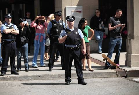 Police and onlookers watch as members of the National Nurses Protest make their way to Daley Plaza.