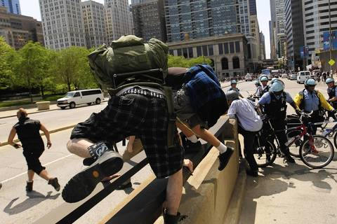 Protesters climb a median to avoid a Chicago Police line at Randolph Street during a march after National Nurses protest rally at Daley Plaza.