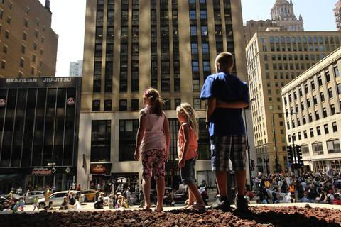 Samantha Kettner, 7, left, Charissa Martz, 7, and Timothy Martz, 9, watch a protest march at North Michigan Avenue and Lake Street after the National Nurses protest rally at Daley Plaza.