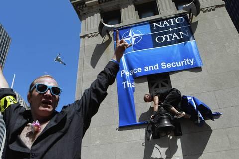 A NATO protester rips a NATO banner from the bridge house on the Michigan Avenue bridge.