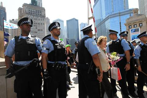 Chicago Police stand guard at the north side of the Michigan Avenue Bridge as protesters try to cross. As well as a pedestrian.