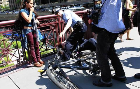 A police officer is assisted after being knocked off her bicycle during a scuffle with a demonstrator on the Michigan Avenue bridge in Chicago.