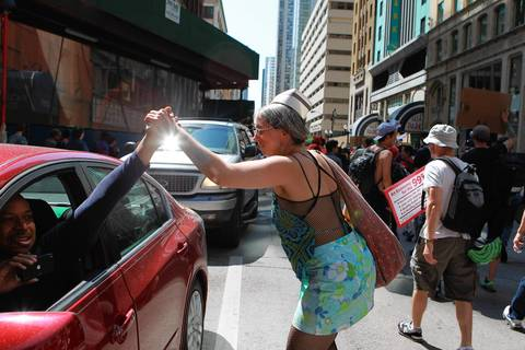 A motorist and demonstrator share a high five in the Loop as a march takes place through downtown streets following a rally at Daley Center Plaza.