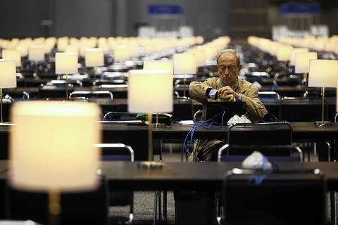Franco Venturini, an Italian journalist with Corriere della Sera, checks the time while working in the press area at McCormick Place in Chicago on Friday, in preparation for the NATO summit that starts on Sunday.