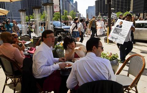 Protestors marching on Wacker Drive toward Michigan Avenue pass by sidewalk cafe diners, in Chicago.