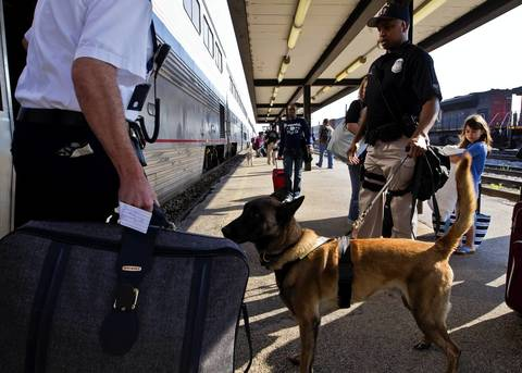 """Amtrak Police officer Stan Bailey, with his dog """"Riot,"""" conducts a security sweep on the Amtrak train, """"City Of New Orleans,"""" arriving in Homewood and headed for Union Station."""