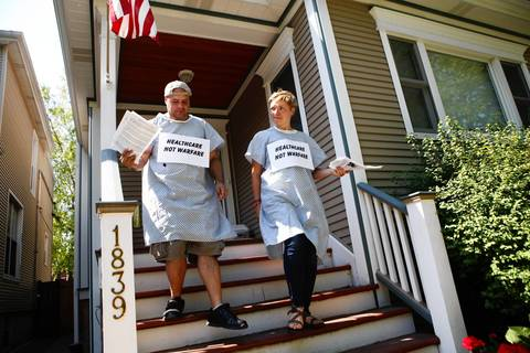 Christopher Colon, Chicago, and Angie Pray, Portland, Ore., wear hospital gowns as they go door to door in Rahm Emanuel's neighborhood, asking his neighbors where they can find mental health care since they mayor closed some of the clinics.