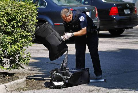 A Chicago police officer looks through a piece of luggage at the scene where a suspicious package was found near Metra tracks seen here in Chicago on Saturday morning. The was removed by the officer and transported in his car. Trains were stopped for an hour and a half on the Metra Electric District line on the South Side while authorities investigated a suspicious package that, according to authorities, turned out to be an empty suitcase.