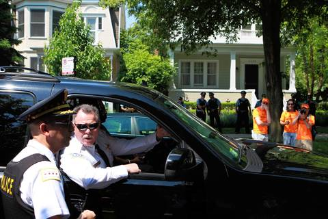 Chicago Police Superintendent Garry McCarthy talks police officers standing guard outside Mayor Rahm Emanuel's house on Saturday. Demonstrators in hospital gowns canvassed the neighborhood, asking neighbors where they can find mental health care since they mayor closed some of the clinics.