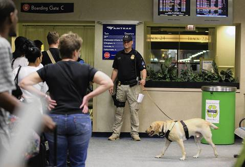 """Amtrak Police K-9 Unit officer Sgt. M. Stoltz handles K-9 dog """"Ryder"""" as he sniffs Amtrak passengers before they board the Saluki southbound train departing Union Station in Chicago on Saturday. The passengers were subject to screenings and searches. The Saluki train runs under McCormick Place where the NATO Summit is taking place May 20-21."""
