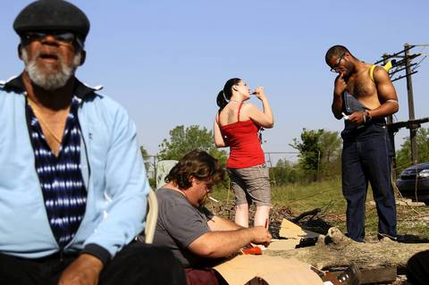 Haley Maine of Lansing, Mich., center, and Robert Fountaine of New York, right, brush their teeth at their campsite outside the Woodlawn Mental Health Clinic.
