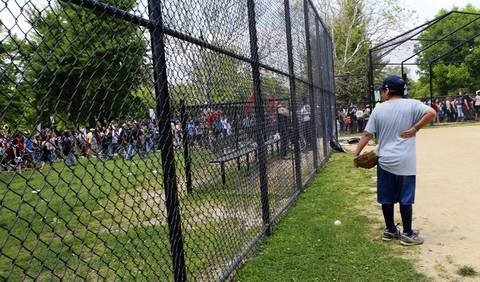 A baseball player at Horner Park watches as about 400 protesters start setting off east toward Mayor Rahm Emanuel's Ravenswood home.