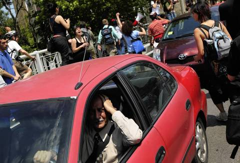 A driver is caught among protesters on Montrose Avenue.