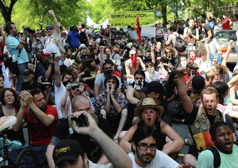 Hundreds of protesters sit in the street outside the home of Mayor Rahm Emanuel.
