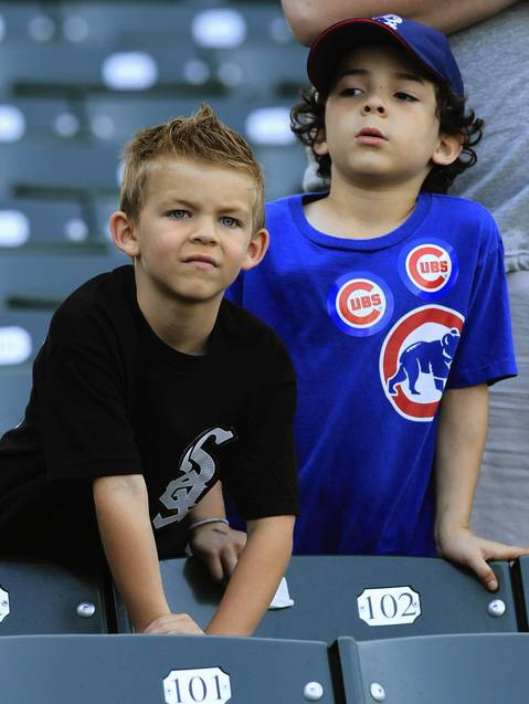 7-year-olds Frankie Barges (Sox fan) and Polo Ramon (Cubs fan) watch batting practice.