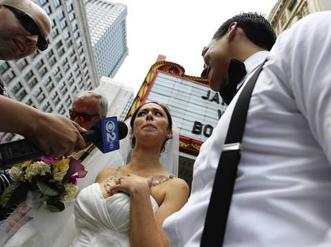 A couple in wedding wear stand outside the Chicago Theatre on State Street.