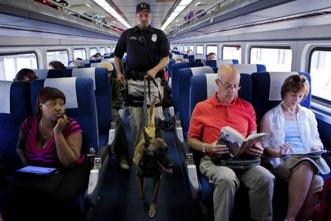 """Amtrak police officer Stan Bailey from Chicago with his dog """"Riot"""" make a security sweep on the Amtrak train """"Saluki"""" at the station in Homewood. Homewood is the last stop for Amtrak before Union Station in Chicago."""