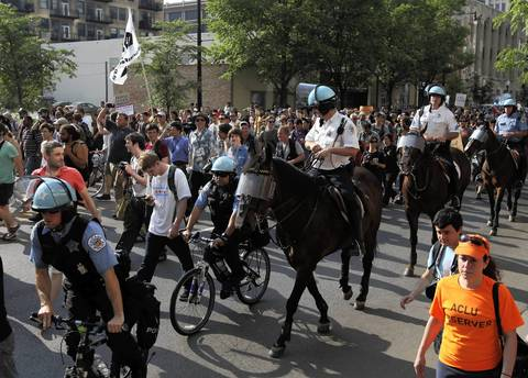 Mounted and bicycle police form a wall to keep protesters going in the same direction.