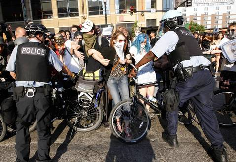 Chicago Police officers use their bikes as shields to push away protesters who tried to break through at Harrison Street and State Street.