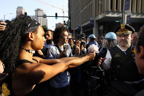 Tamara Jasmine offers a flower to a member of the Chicago Police at Harrison Street and State Street.