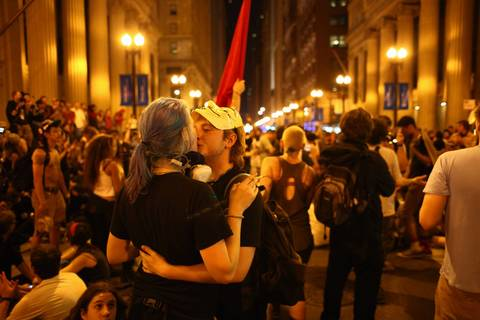 Occupy protesters from Boston kiss during an unorganized march near the corner of Jackson and LaSalle in the Chicago Loop.