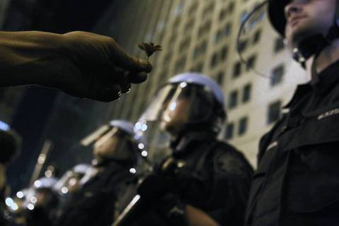 A protestor offers a flower to Chicago police standing in front of the Chicago Board of Trade Building.