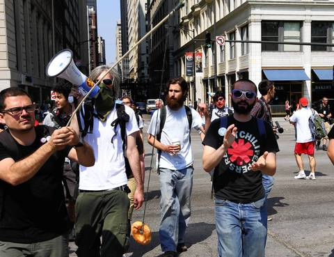 Protesters, one carrying a fishing pole with a donut as bait, walk to Grant Park for an anti-war march and rally.