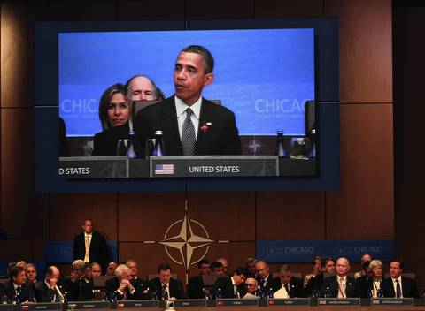 U.S. President Barack Obama appears on a large monitor as he speaks to attendees during the opening session of the North Atlantic Council of the 2012 NATO Summit.