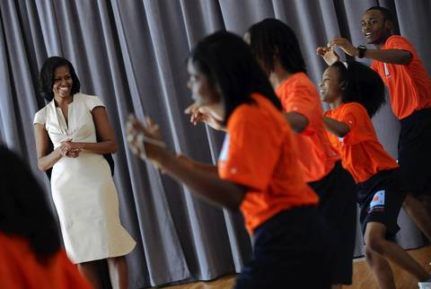 First Lady Michelle Obama checks out a hip hop aerobics class while she and other NATO leaders' spouses and companions tour the Gary Comer Youth Center on the South Side of Chicago