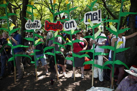 "Protesters hold a row of corn stalks with the phrase ""don't trade on me!"" at the anti-war march and rally during the NATO 2012 Summit."