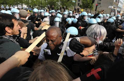 A protester breaks a stick over the head of a Chicago police officer as the two groups clash at Cermak Road and Michigan Avenue.