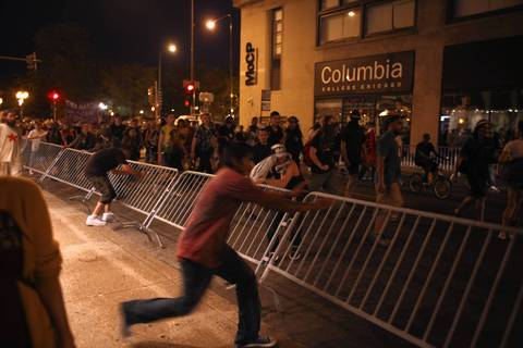 Protesters knock over a barrier at VanBuren Street and Wabash Avenue.