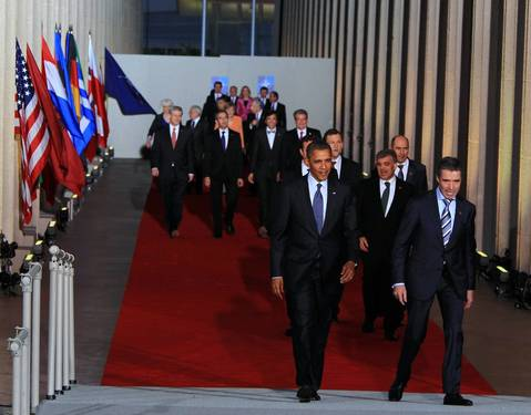 U.S. President Barack Obama, left, and NATO Secretary General Anders Fogh Rasmussen lead NATO leaders down a red carpet at Soldier Field for the NATO family photo.