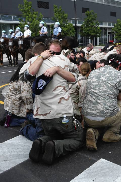 Iraq veterans gets highly emotional as they all kneel on the ground after throwing away their medals.