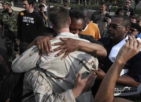 Rev. Jesse Jackson hugs veterans during an anti-NATO protest as they march west on Cermak Road.