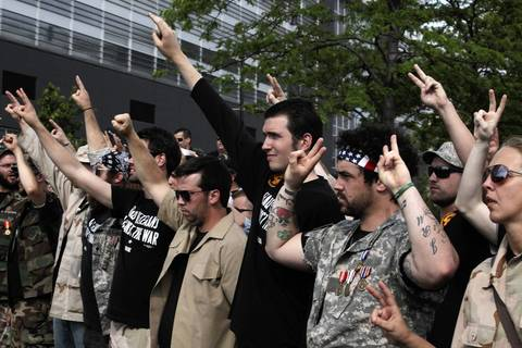 Members of Iraq Veterans Against the War raise their hands in solidarity before they each went onstage and threw away their medals.